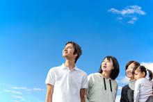 1組の夫婦と1組の親子が皆んな斜め上を見つめている。目標、希望、期待、明るい未来と将来イメージ