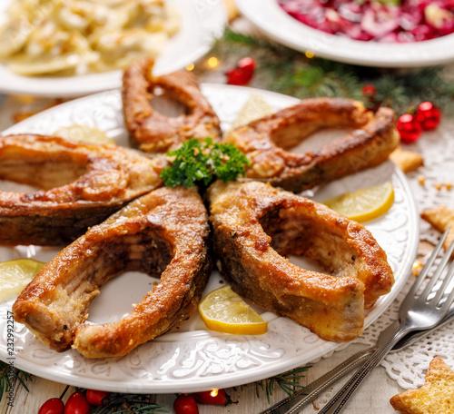 Fried carp fish slices on a white plate, close up. Traditional christmas eve dish. Polish Christmas food