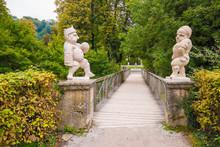 Two White Marble Dwarfs At The Entrance To The Dwarf Garden (Zwerglgarten) Playing Pallone Game. Dwarf Garden Is A Part Of Mirebell Palace Gardens (Mirabellgarten) In Salzburg, Austria