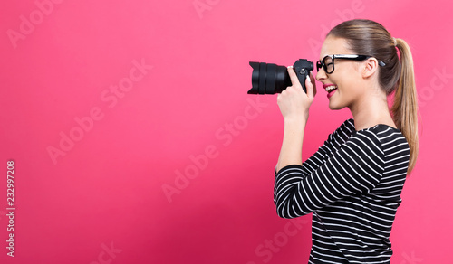 Fotografie, Obraz Young woman with a professional digital SLR camera on a pink background