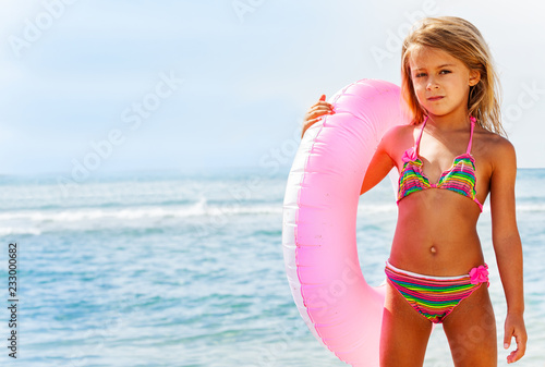 Beautiful girl posing with swim ring on the beach Wallpaper Mural