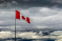 Canadian Flag Blowing In High Winds Against A Stormy Clouded Sky
