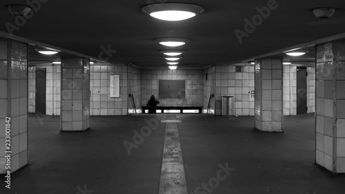 A woman is walking down the stairs in the subway station