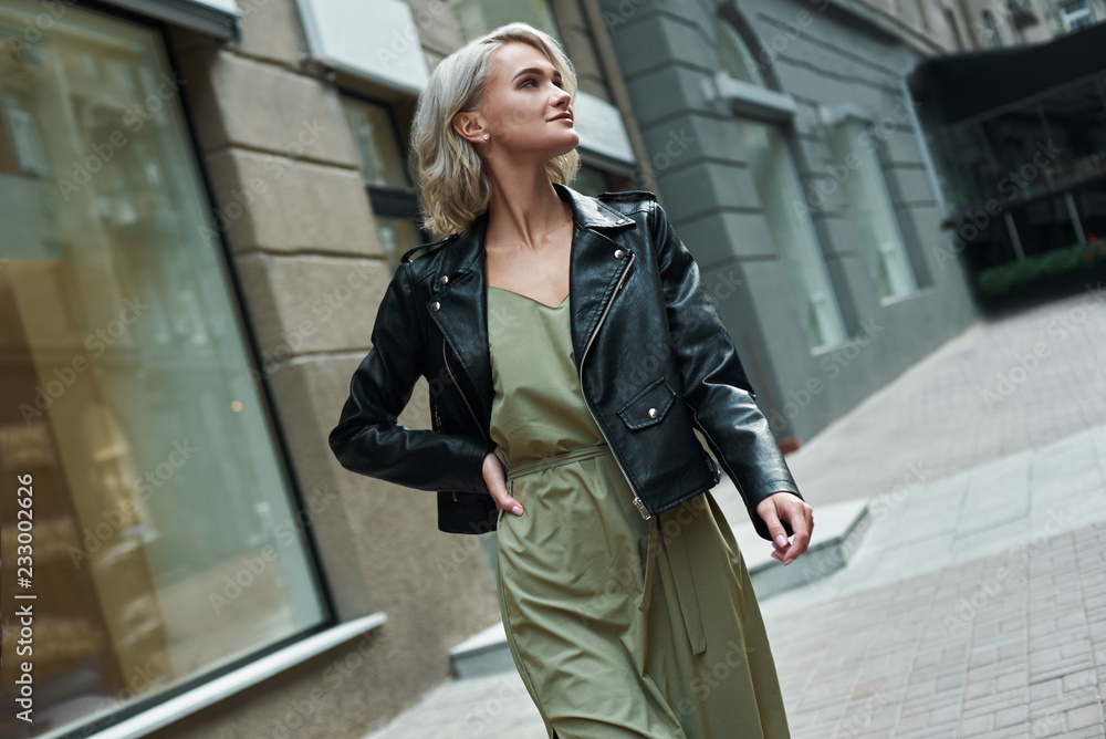 Fototapeta Fashion. Young stylish woman walking on the city street looking aside smiling happy