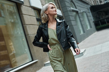 Fashion. Young Stylish Woman Walking On The City Street Looking Aside Smiling Happy