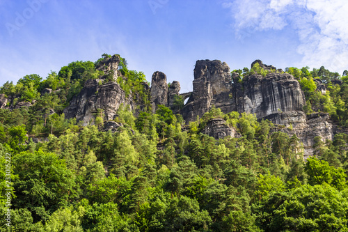 Foto  View up on stone formations and the famous Bastei bridge in Saxony, Germany