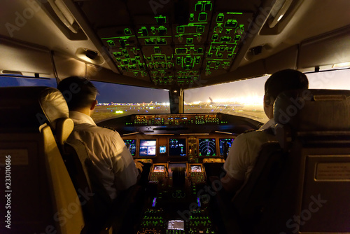 Fotografia  Inside cockpit on ground at an airport, both pilots are operating the airplane moving to the runway