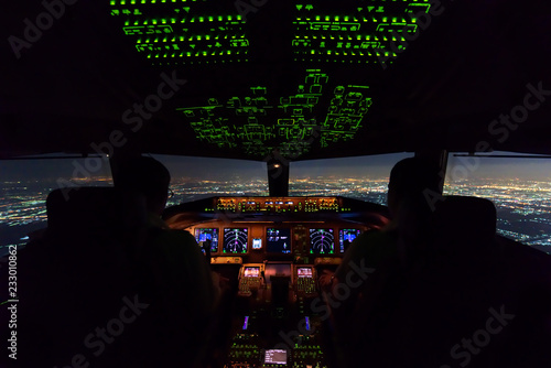 Photo Two pilots are flying the airplane in final approach phase to the runway in night time
