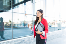 Businesswoman Holding Coffee Cup And Folder Outside Work