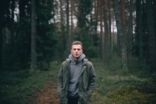 Caucasian Young Man In A Forest In A Green Jacket.
