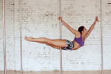 Girl crosses her legs while she performs pole dance in the studio