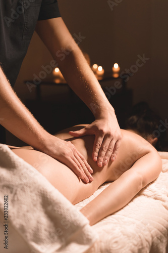 Close-up male hands doing healing massage with oil to a young girl in a dark cosmetology office Fototapete