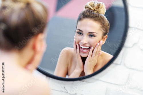 Fotografia Young woman cleaning face in bathroom mirror