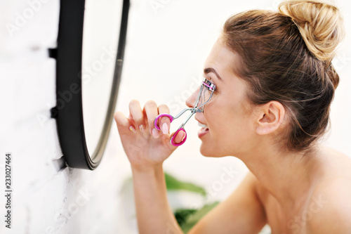 Photo Young woman using eyelash curler in bathroom