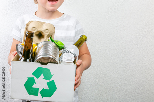 Boy holds box with recyclable materials