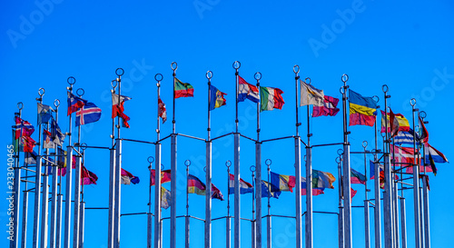 Photo  Flags of European countries on flagpoles against the blue sky.