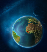 Planet Earth With Highlighted Guinea In Space With Moon And Milky Way. Visible City Lights And Country Borders.