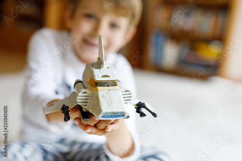 Happy little kid boy playing with space shuttle toy. Cute child in having fun in the morning before school. Selective focus on old plastic toy. Blond kid on background.