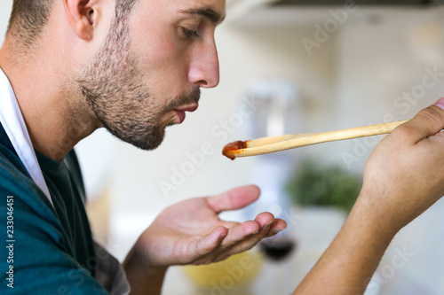 Fototapeta Handsome young man tasting the fried with wooden spoon in the kitchen at home. obraz