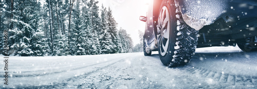 Closeup of car tires in winter on the road covered with snow Fototapet
