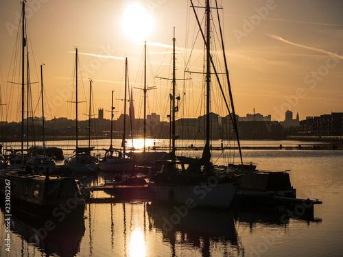 Fototapeta Sunrise in Preston Docks with Yacht masts and cityscape
