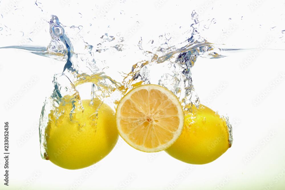 Fototapeta Two lemons and lemon slice spash in water on white background