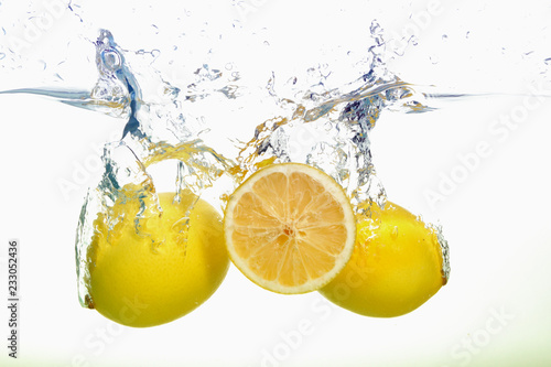 Fototapeta Two lemons and lemon slice spash in water on white background obraz