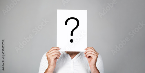 Man a question. Doubtful man holding Question Mark. Problems and solutions. Question mark, symbol. Pensive male. Getting answers. Portrait of man, peeking behind of interrogation symbol. Male isolated
