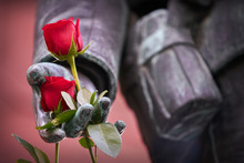 Close Up Roses On Soldier Statue. Red Roses On A Close Up Of A Statue Of A World War One Soldier.