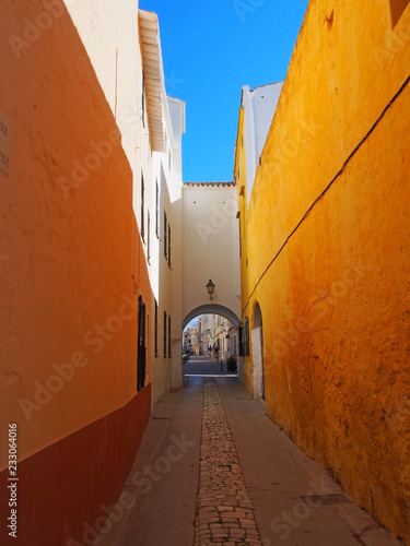 Tuinposter Smal steegje a long narrow alley in ciutadella town menorca with a bright yellow wall and archway at the end with a blue summer sky