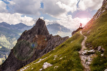 Single Hiker On A Narrow Mountain Path In The Sunlight