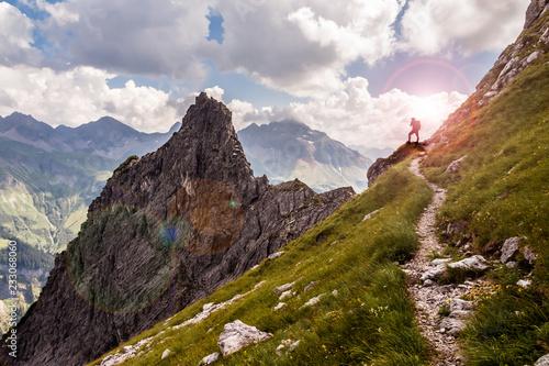 Single Hiker on a Narrow Mountain Path in the Sunlight Fototapete