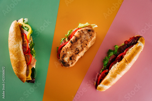 Wall Murals Snack Top view of a group of fresh deli sandwiches on top of colorful backgrounds.