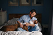 canvas print picture - Portrait of middle age Caucasian father with newborn baby. Dog pet laying on bed. Man parent holding child in hands. Authentic lifestyle documenatry moment. Single dad family life.