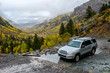 Rainy Day on Mountain Trail - On a rainy and foggy autumn day, a SUV's driving through a mountain creek on rugged Black Bear Pass trail, near Telluride, CO, USA.