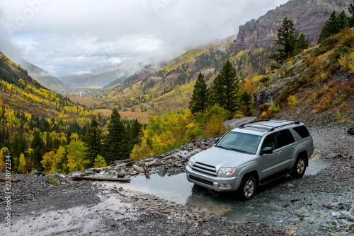 Obraz Rainy Day on Mountain Trail - On a rainy and foggy autumn day, a SUV's driving through a mountain creek on rugged Black Bear Pass trail, near Telluride, CO, USA. - fototapety do salonu