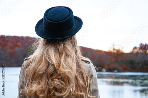Fotografie, Tablou  Woman in hat and warm autumn clothes looking at lake
