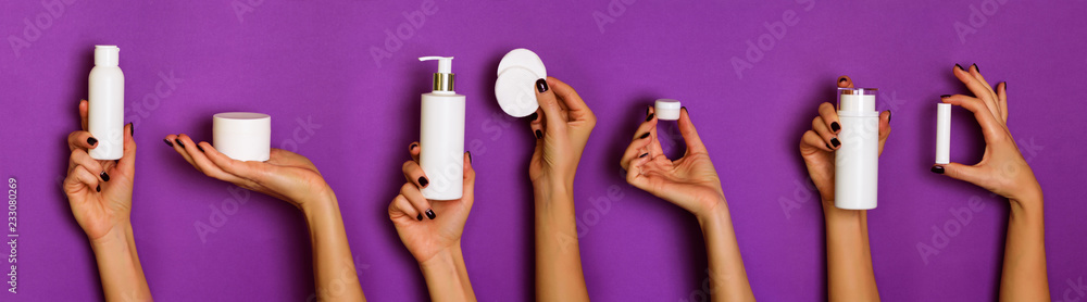 Fototapeta Female hands holding white cosmetics bottles - lotion, cream, serum on violet background. Banner. Skin care, pure beauty, body treatment concept