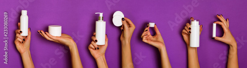 Obraz Female hands holding white cosmetics bottles - lotion, cream, serum on violet background. Banner. Skin care, pure beauty, body treatment concept - fototapety do salonu