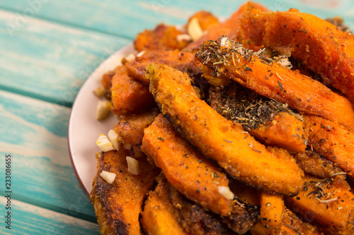 Fotografía  Chopped baked pumpkin with spices at blue background
