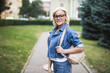 Young beauty woman in eyesglasses posing in the street with backpack, blonde hair, outdoor closeup portrait.