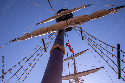 View of a ship mast with two spars, shrouds and collapsed sails from below Fototapete