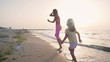 Young mother with her little daugter running on the beach near the water slowmo
