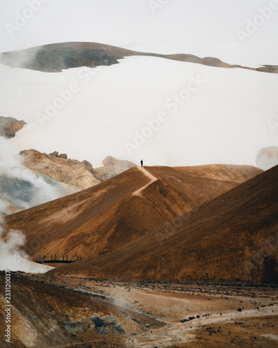 Tiny hiker on Iceland volcanic landscape