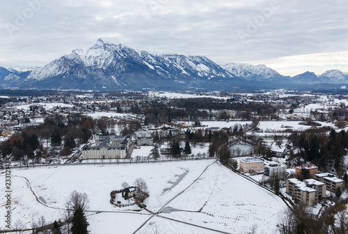 Papiers peints Alpes panoramic winter view of the historic center of Salzburg Austria surrounded by the Alps covered with snow in a foggy haze