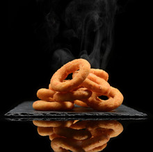 Hot Calamari Or Onion Rings On Black Stone Plate And Steam Smoke On Black