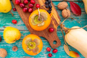 Fototapeta Autumn harvest, fruits and autumn vegetables on a wooden background.