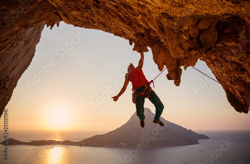 Foto Male rock climber hanging on cliff with one hand at sunset