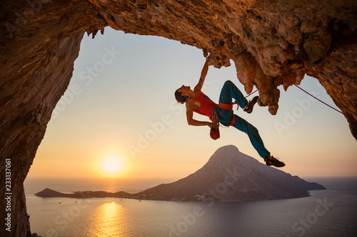 Male rock climber hanging with one hand on challenging route on cliff at sunset