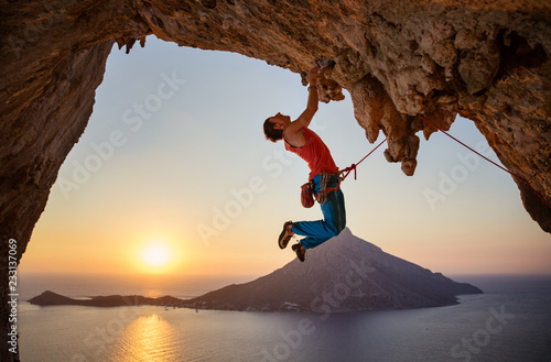 Male rock climber hanging with one hand on challenging route at sunset - 233137069